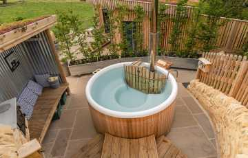 A log fired hot tub sits a sheltered spot on the side of the Malvern Hills, overlooking the wooden lodge and the countryside