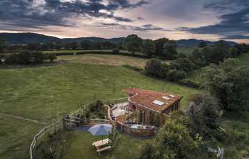 A contemporary lodge, big enough for 4 sits in the middle of fields with the Malvern Hills in the background
