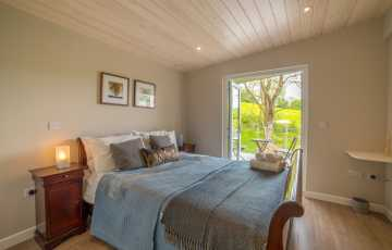 The master bedroom with lovely linens on the double bed and access to the cabins terrace