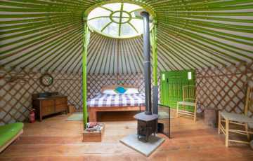 A log burner sits in the middle of the family yurt
