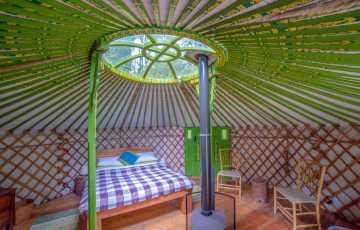 The handmade, king size double bed sits under the crown of the decorate family yurt for great star gazing
