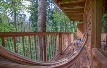 A full-size hammock is positioned on the treehouse terrace with the woodland below you and trees stretching up to sky right by you