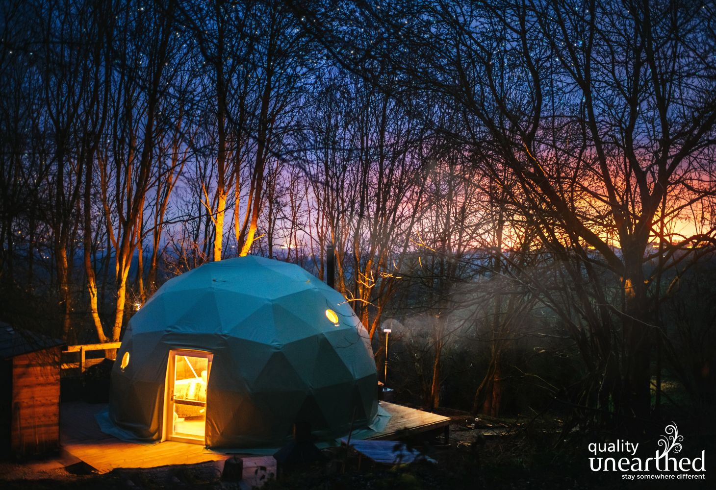 The sun sets through the Shropshire woods surrounding the geodome