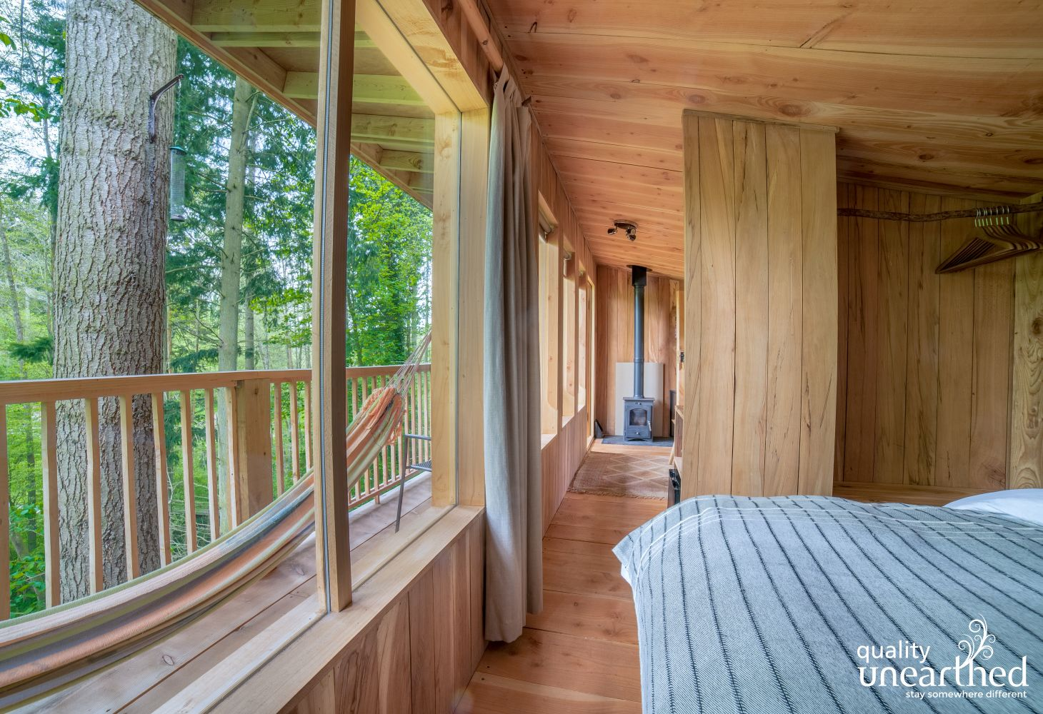 The double bed in the wooden cabin has amazing views across the welsh woodland
