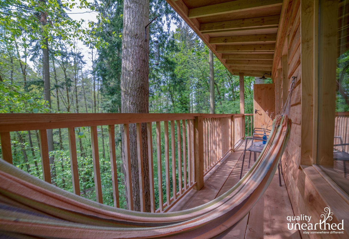 A full size hammock on the terrace of the wooden cabin
