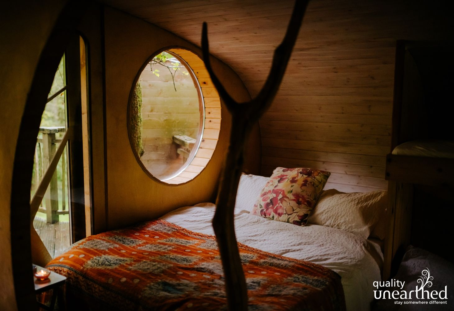 A colorful double bed looks cosy with the lichen on a tree outside the window reminding you of the natural woodland setting of these 6 welsh treehouses