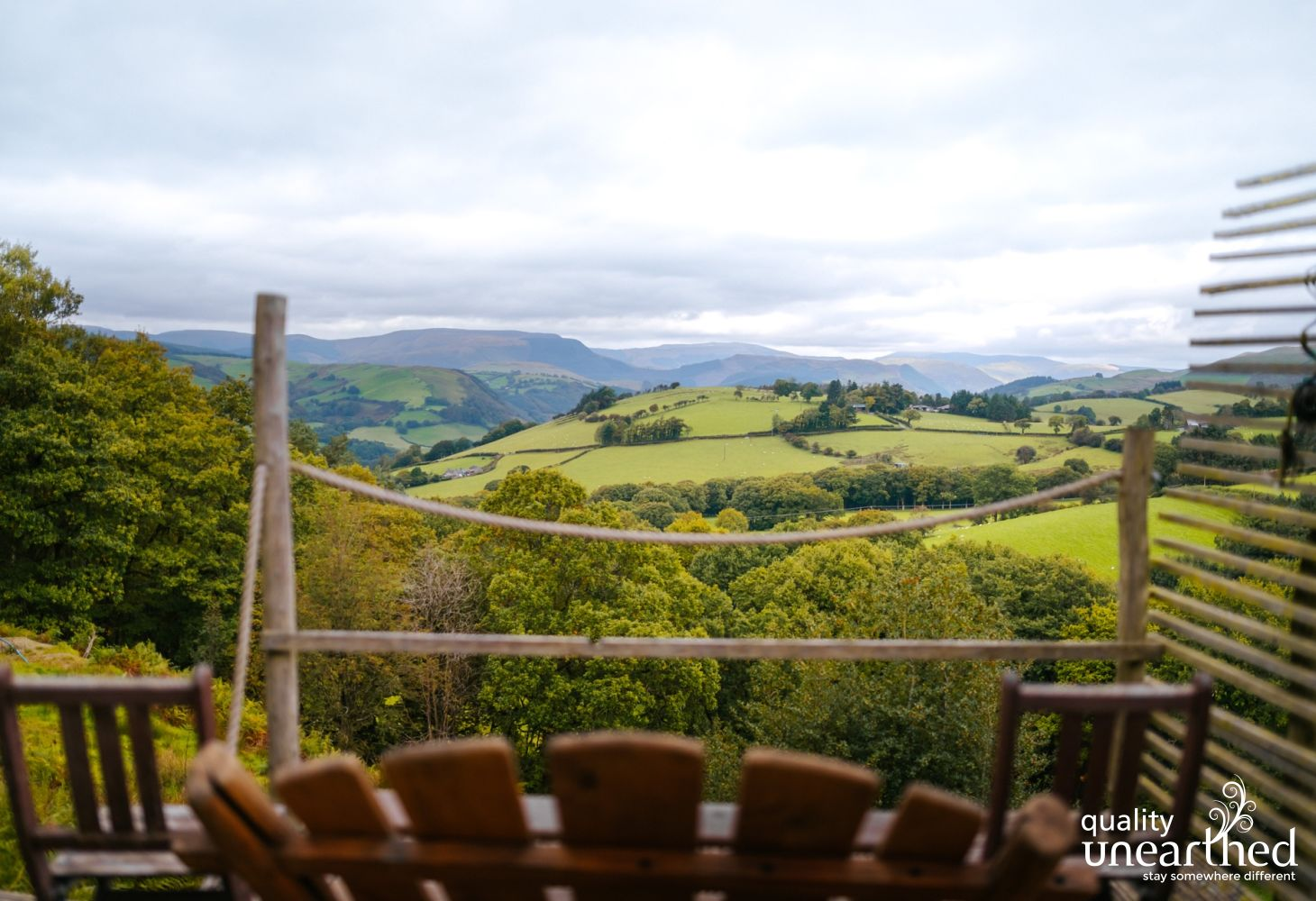 A wooden bench takes full advantage of the view from the treehouse terrace across rolling hills, the woods and the Cader Idris mountains