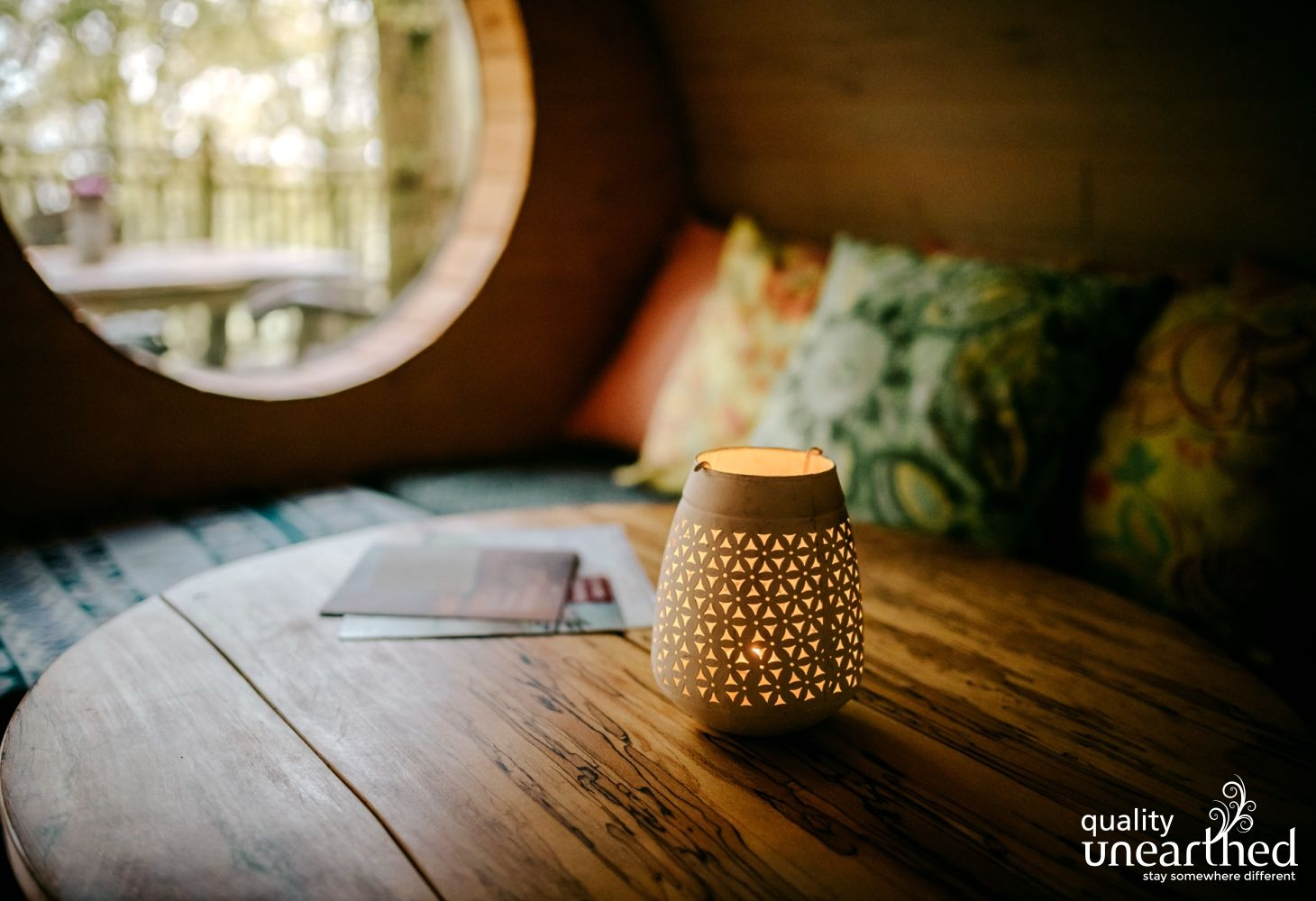 A Moroccan style candle sits in the foreground. Behind this is a handcrafted porthole style window which looks out from this romantic treehouse to the woodland