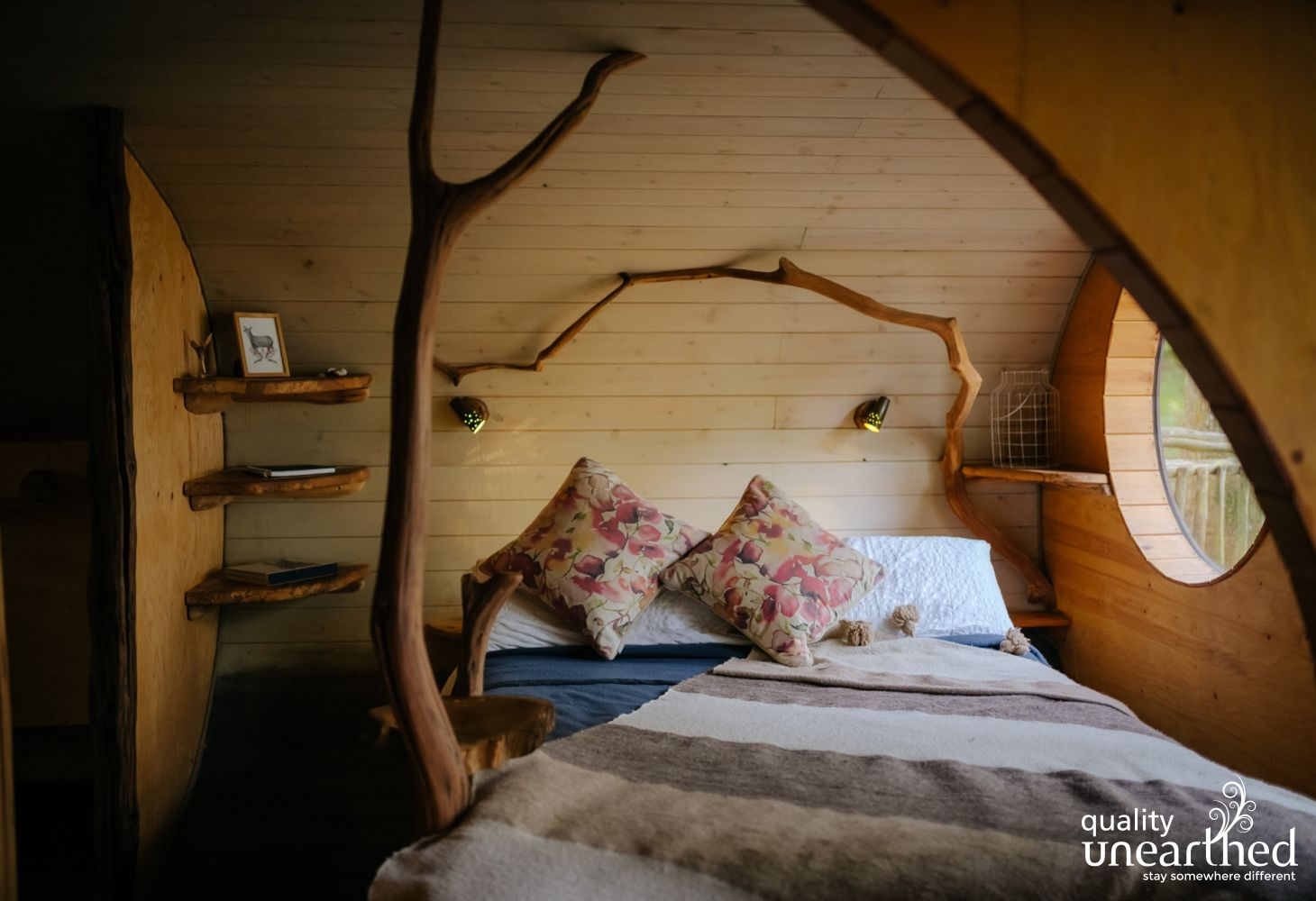 Double bed in a pine clad treehouse bedroom. Hand carved bookshelves and decorative tree structures add to the romantic treehouse atmosphere