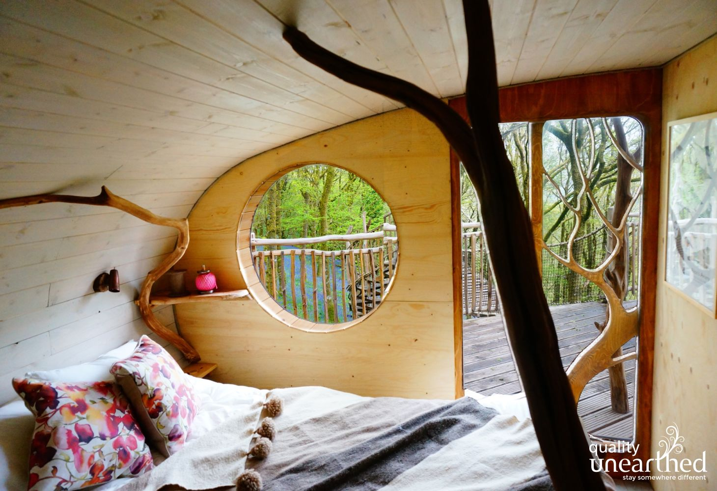 Sight of bluebells from the handcrafted porthole treehouse window of this double bedroom which is clad in pine with lovely linens