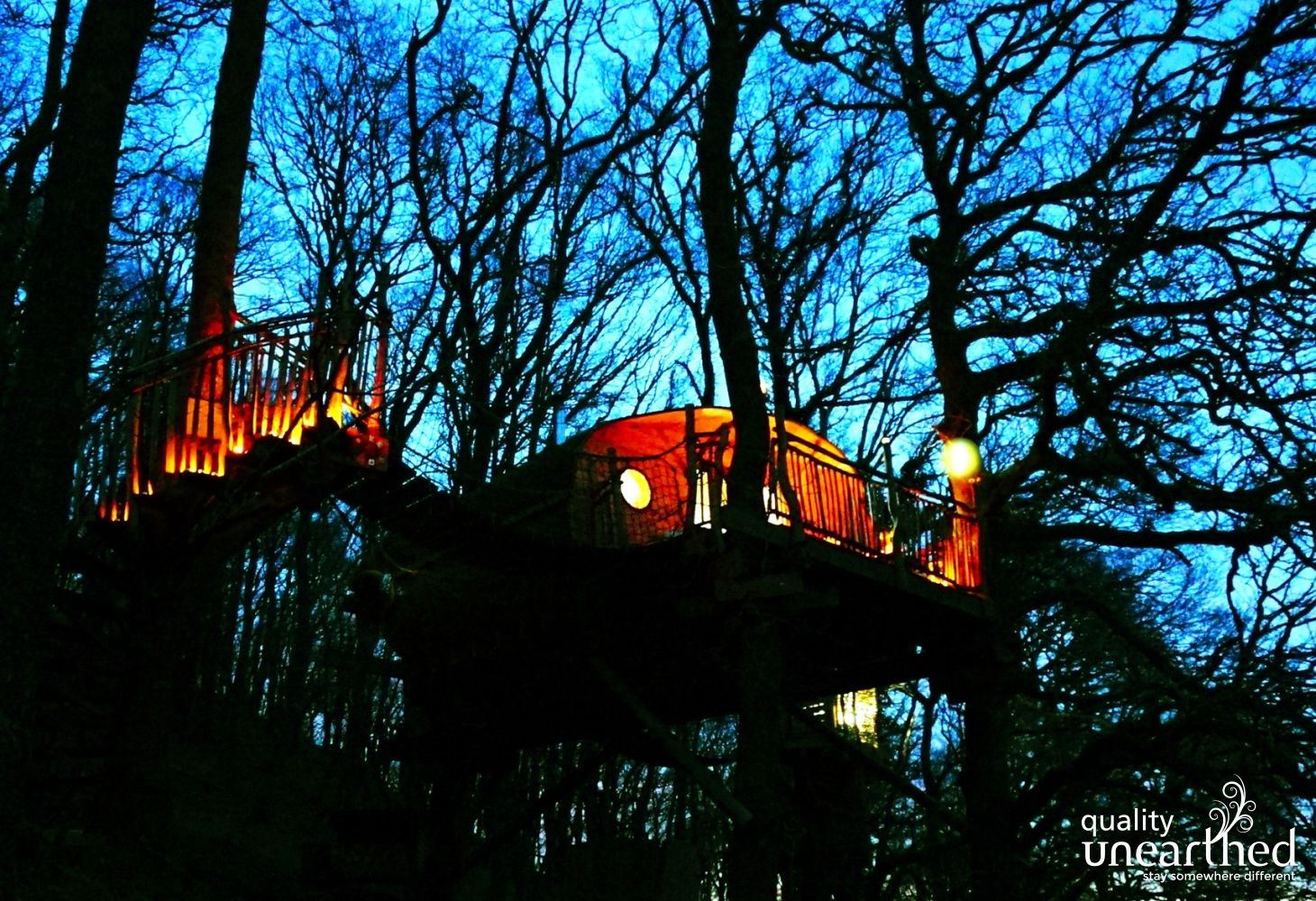 A treehouse big enough for a family sits high above the photographer on stilts in the middle of the woods. It is dusk and the lights are on