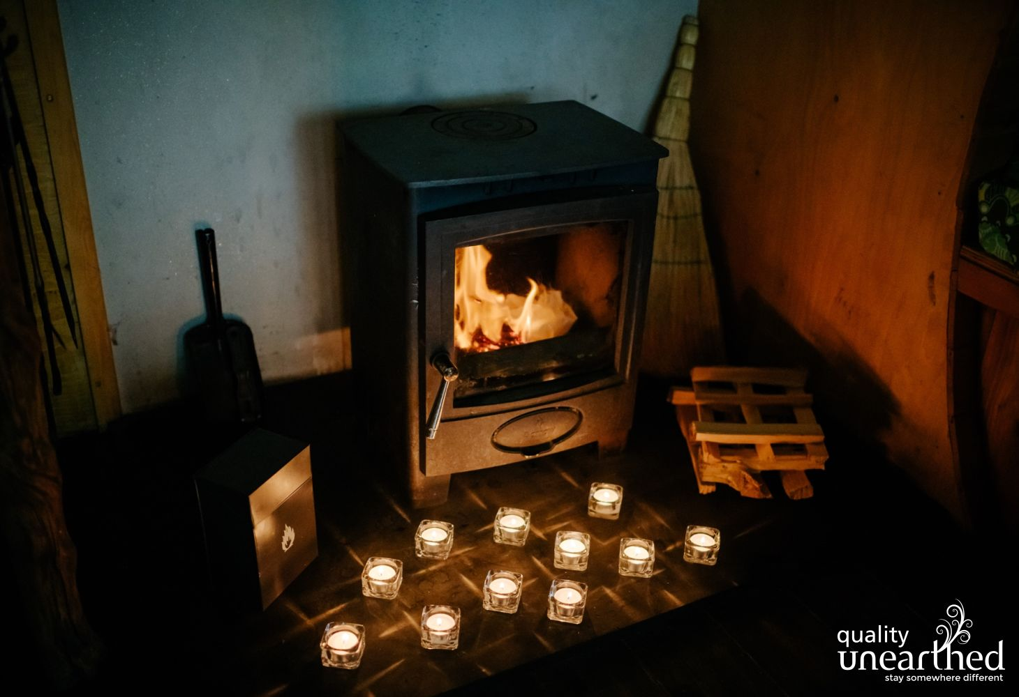 A romantic scene is created with a cosy looking wood burner. Tea lights flicker on the hearth