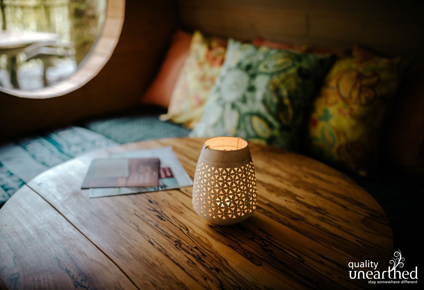 Candle on a coffee table in a reading nook with views over the woods from the treehouse