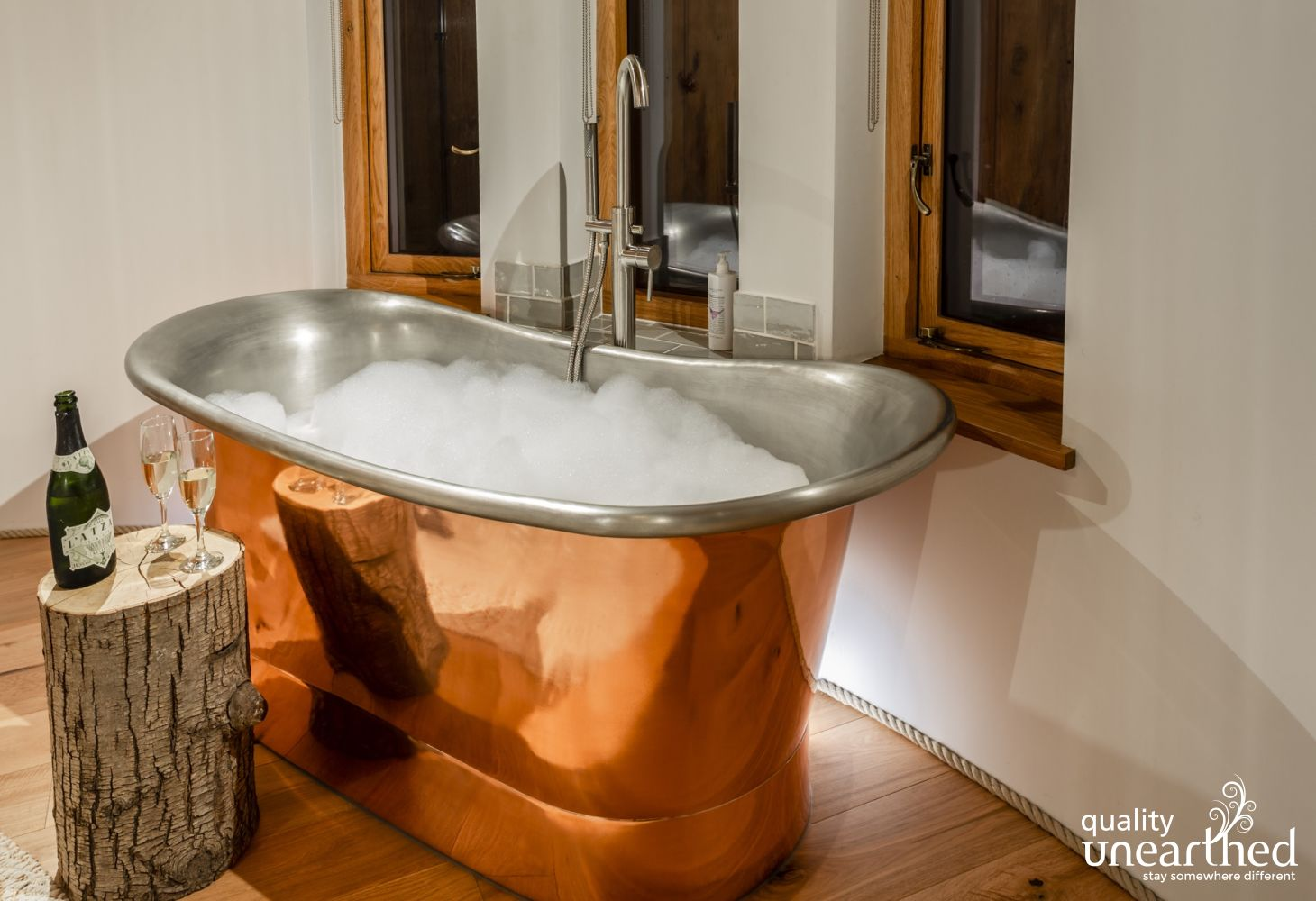 Luxury copper bath full of bubbles and champagne in the master bedroom. Dark night sky outside the treehouse