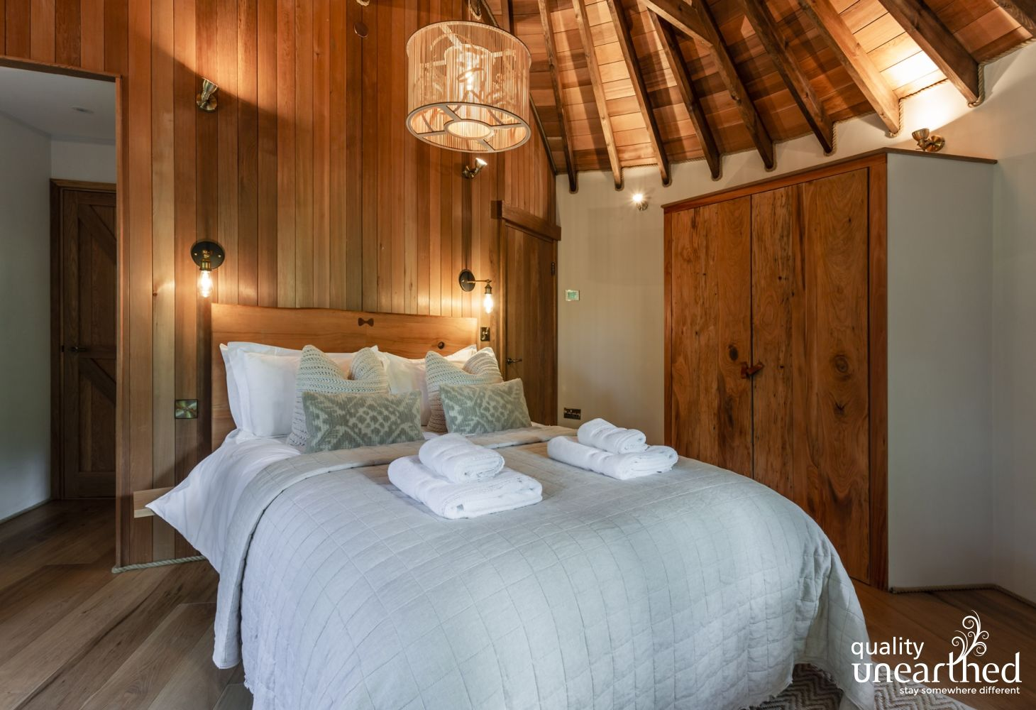 A king size 5 star luxury bed with plush linens, under exposed eves with windows to the Sussex woodland