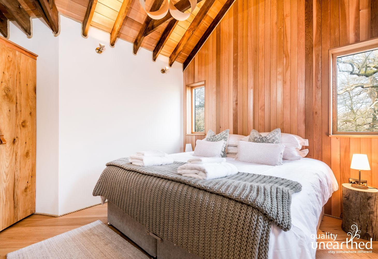 A super king sized double bed under the cedar eves of the second treehouse bedroom with windows to the woodland