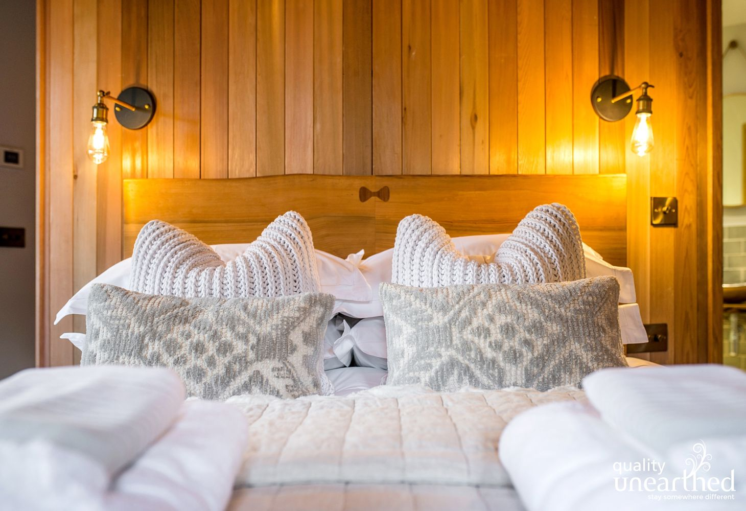 A wooden king sized bed with crisp linens and plump cushions against a cedar wall panel in the master bedroom of the treehouse