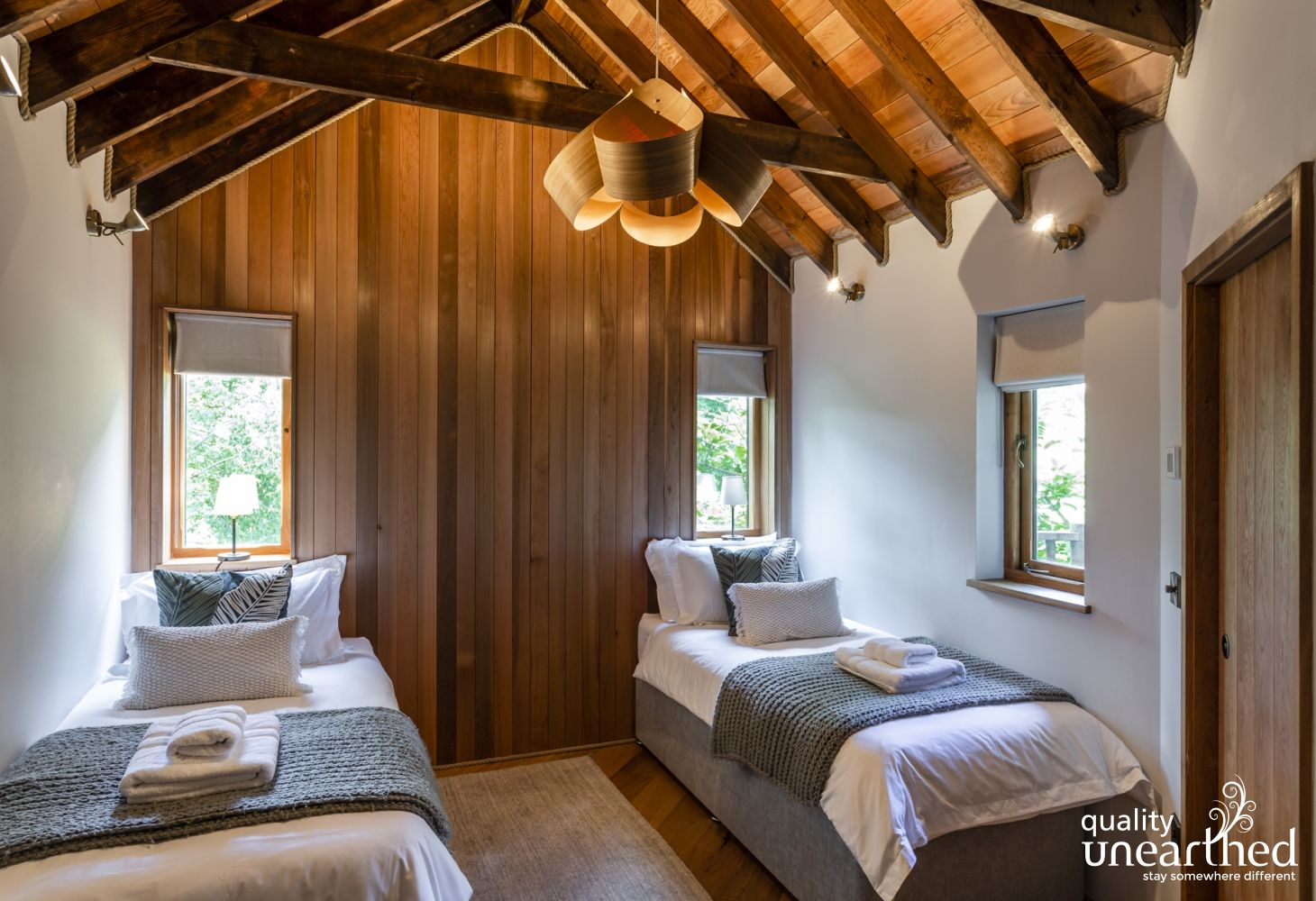 The treehouse twin bedroom, great for kids under the open wooden beams with cedar decorative planks and windows looking across the Sussex woods