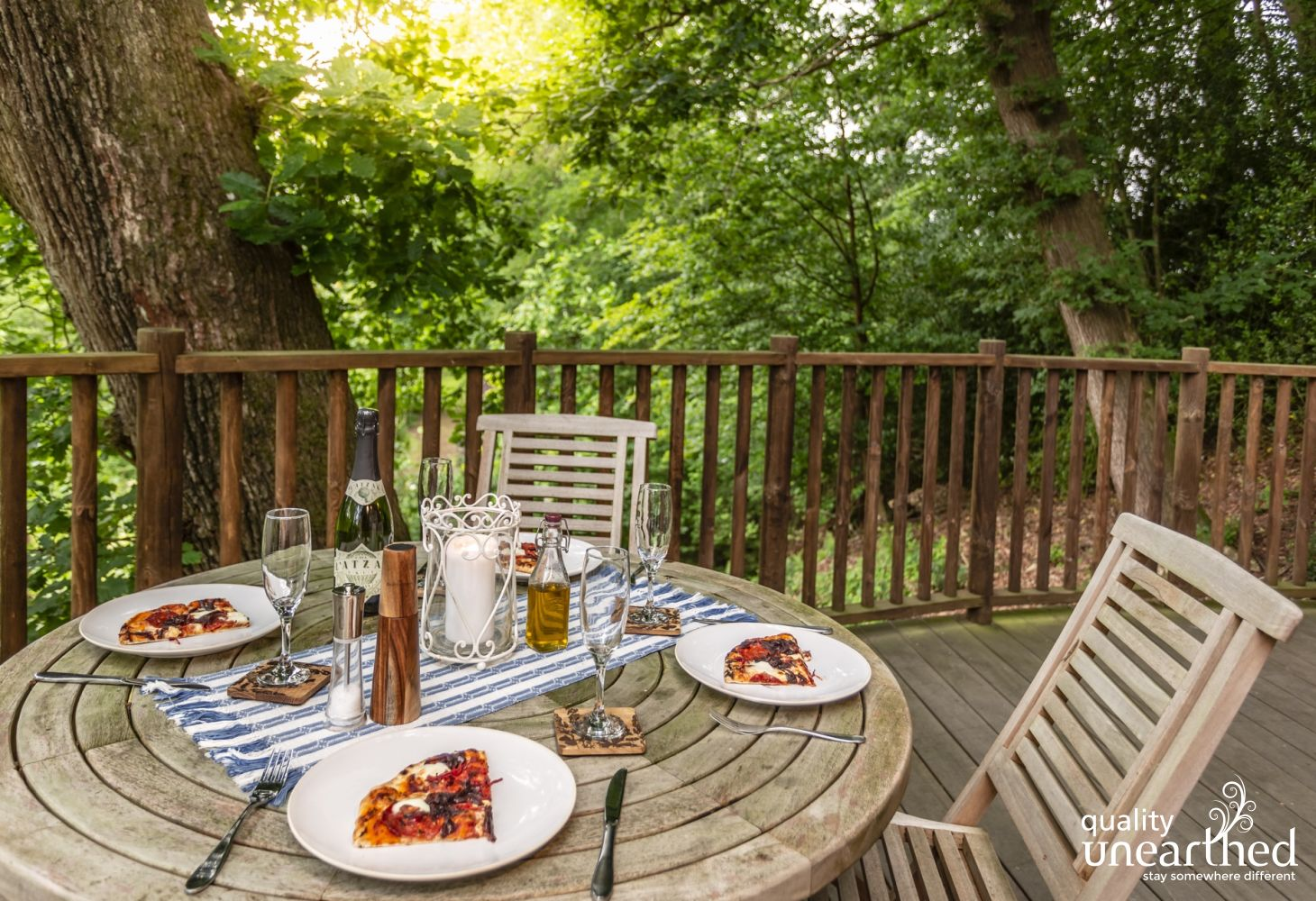 Dining table on the treehouse terrace laid with pizza and lovely crockery under the boughs of the Sussex woodland