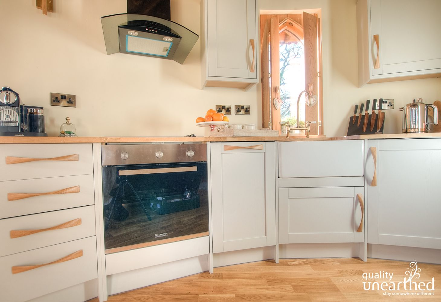 A neutral stylish kitchen with a picture window from the treehouse out to the Breacon Beacons