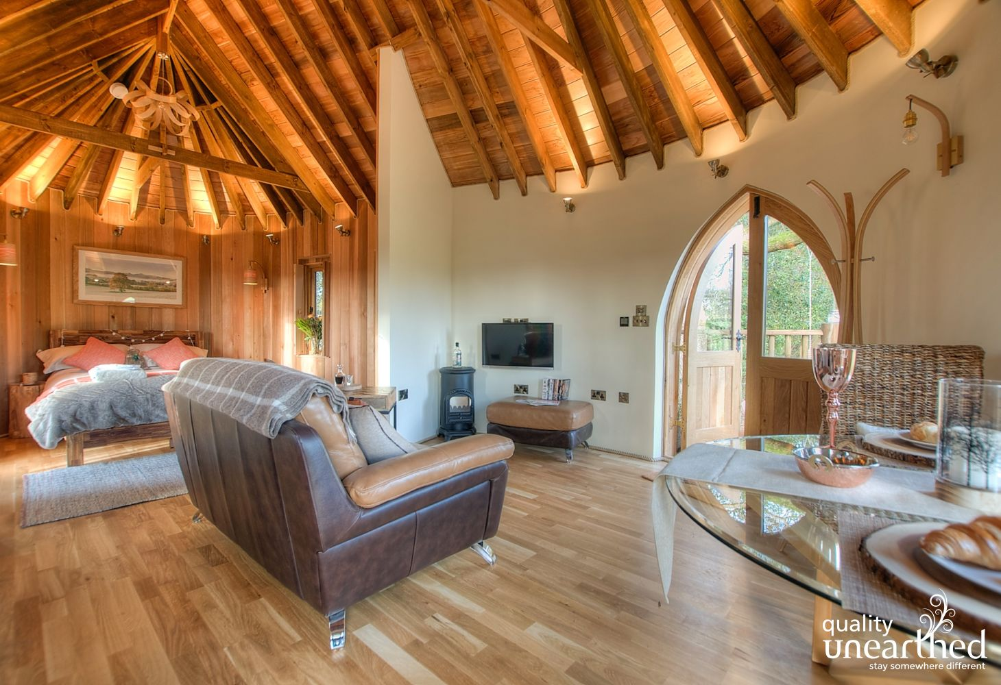 Wooden floors under the open wooden beams of the treehouse. We see the double bed, sofa for 2 and dining table
