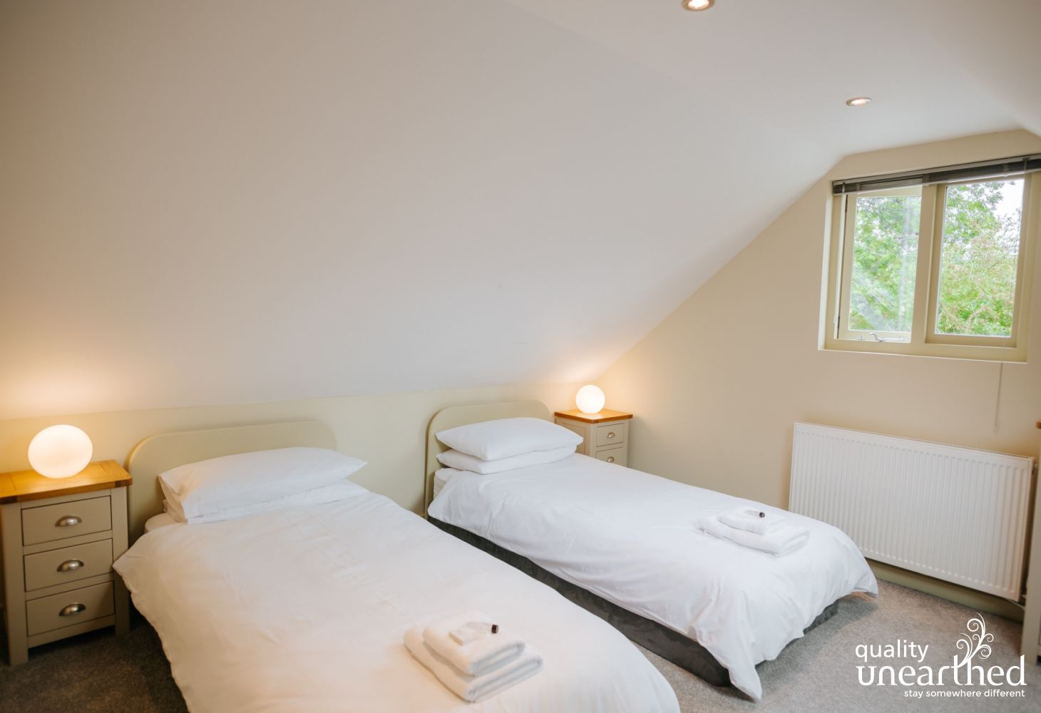 Twin bedroom with a window to the Cotswold woodland setting