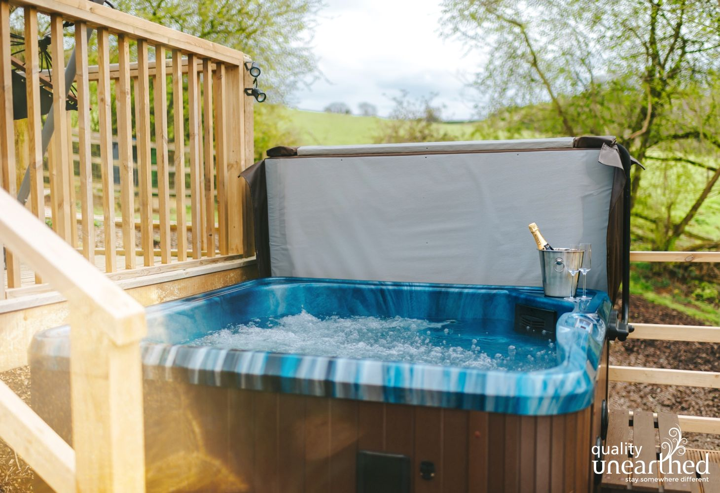 A hot tub sits on the treehouse terrace