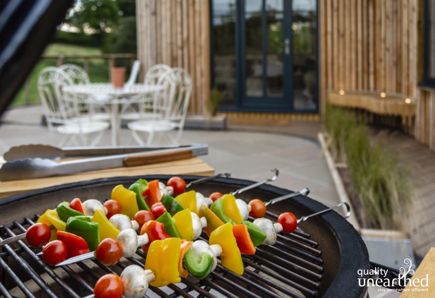 A bbq sits on the terrace right outside the wooden luxury lodge