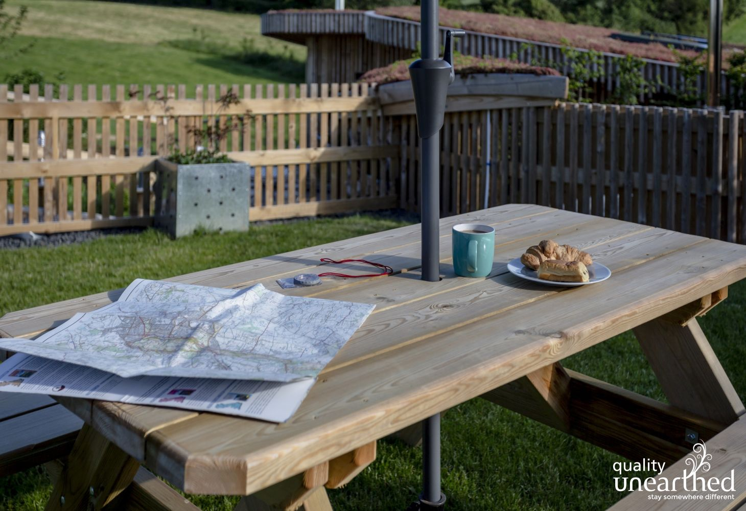 A classic picnic bench with a parasol on the lawn above the family lodge and a map to plan walking in the Malvern Hills