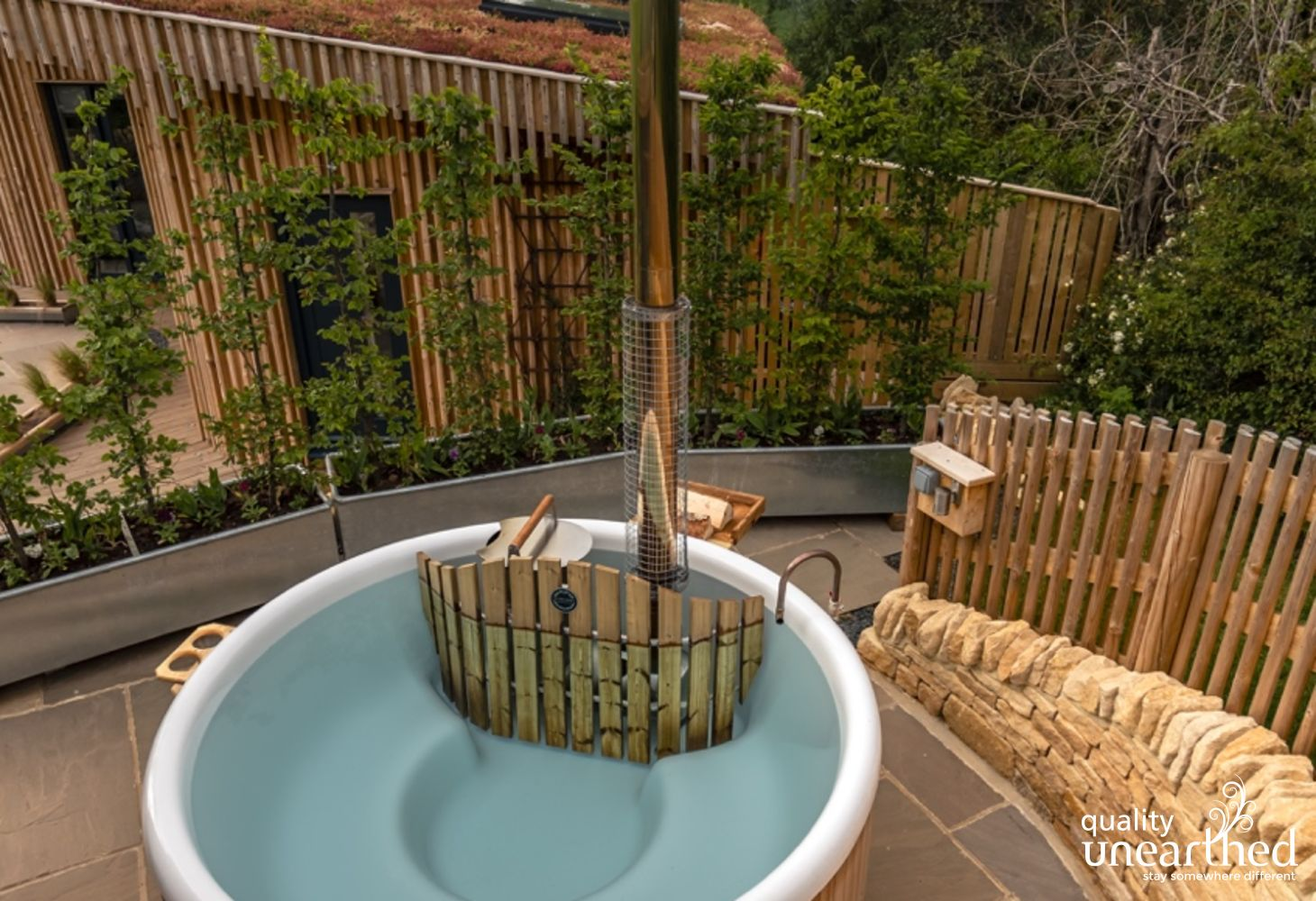 The Swedish log fired hot tub sits on a terrace with view across the Malvern countryside, over the sedum roof of the handcrafted luxury glamping lodge