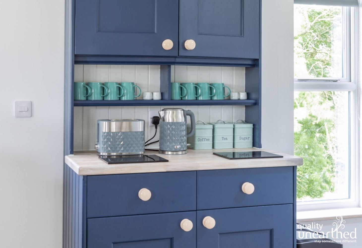 A welsh dresser painted in a classic farrow and ball shade sits in the kitchen of the luxury wooden lodge