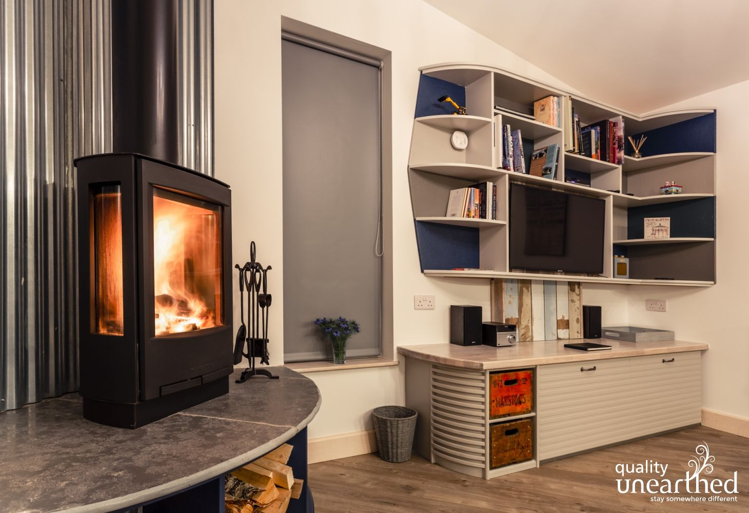 A contemporary log burner adds to this cosy wooden cabin. A smart TV sits in a bookshelf with a music system