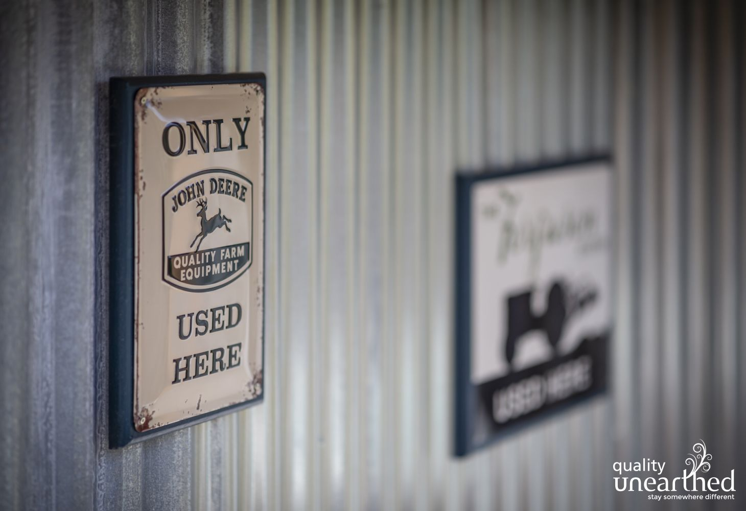 An antique John Deere sign hangs of the wall of this luxury countryside cabin