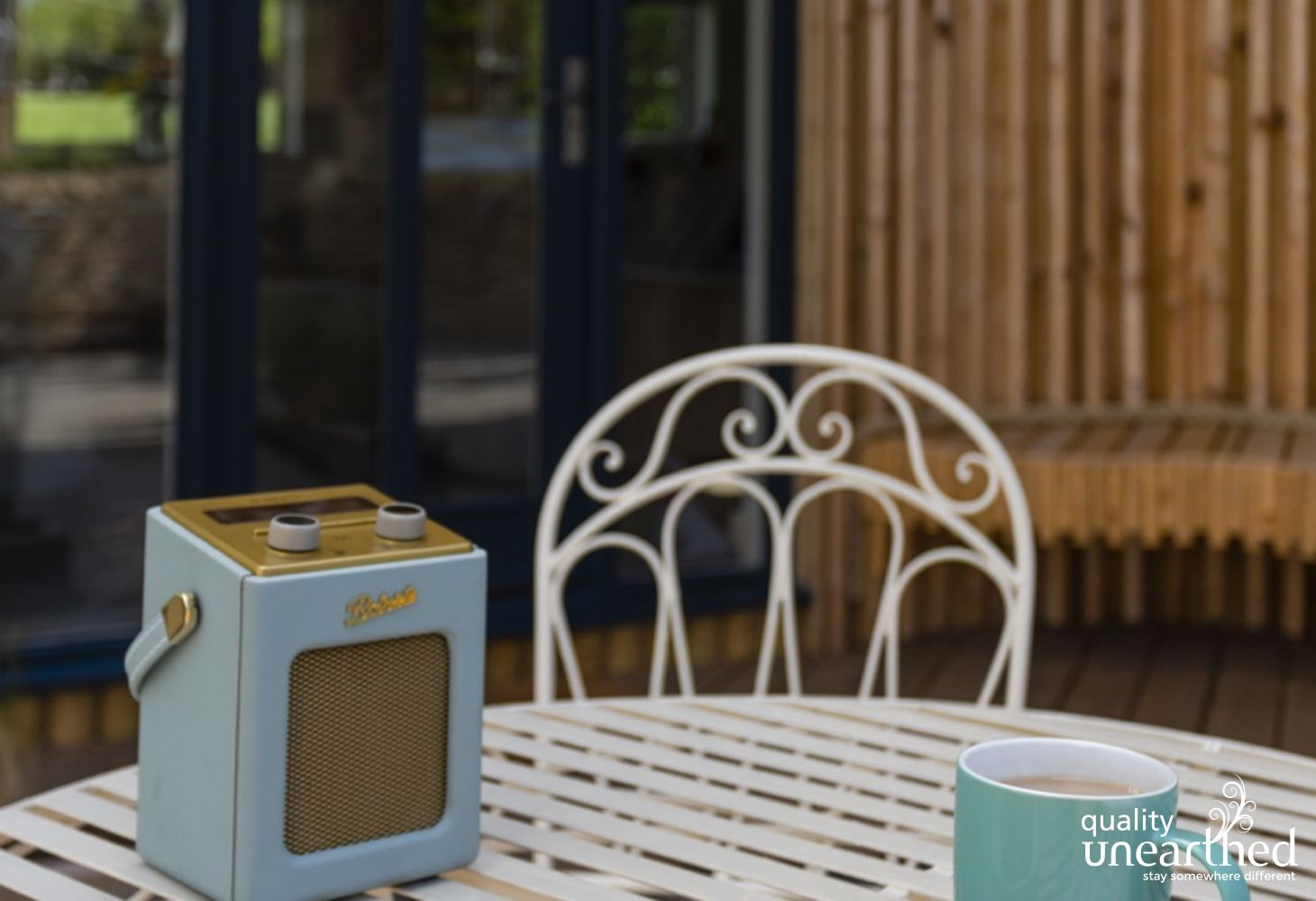 A Roberts radio sits on a French style outdoors table with coffee and pastries, right outside the contemporary wooden lodge