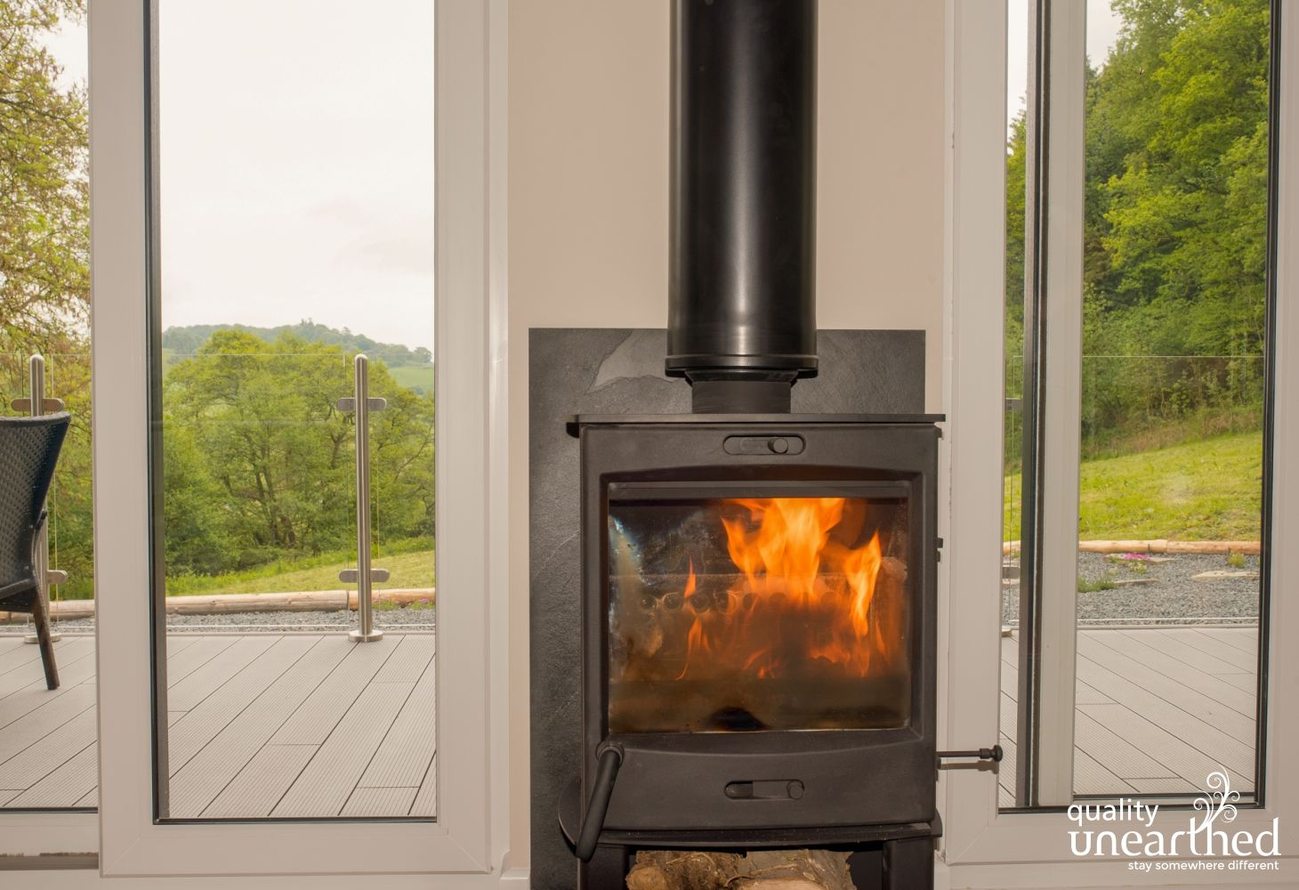 The flames of the fire burner flicker in the cabin, with the Mid Wales countryside near Newton in the background