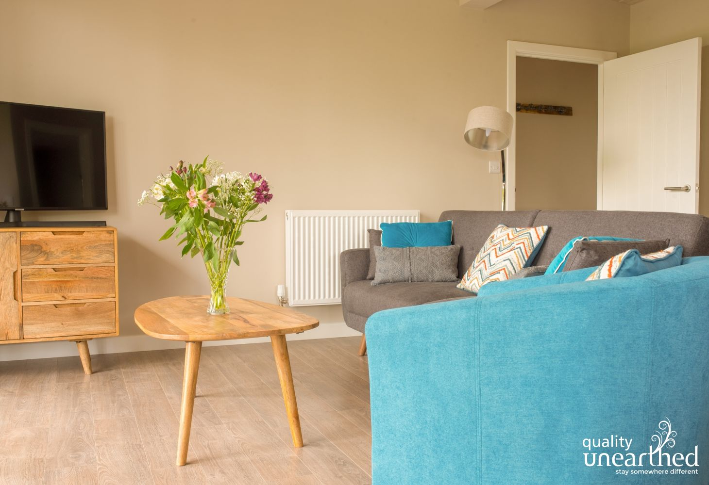 The living area in the open plan wooden cabin is stylish with a powder blue sofa, TV with Netflix and wifi