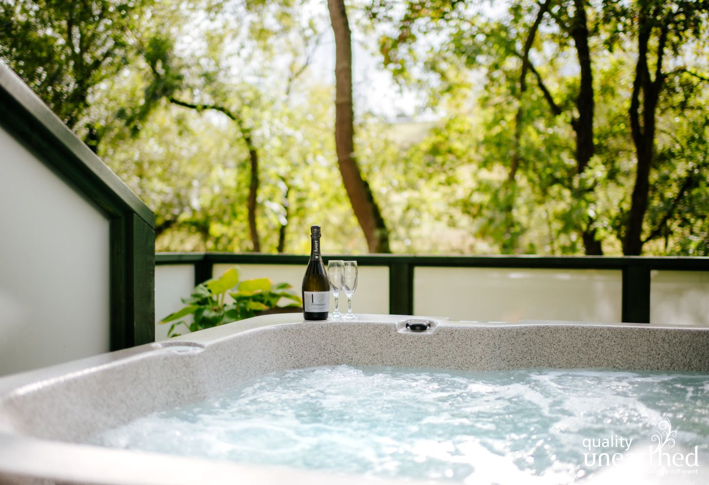 A full size hot tub sits on the treehouse with the Cotswold woodland the other side of the treehouse terrace