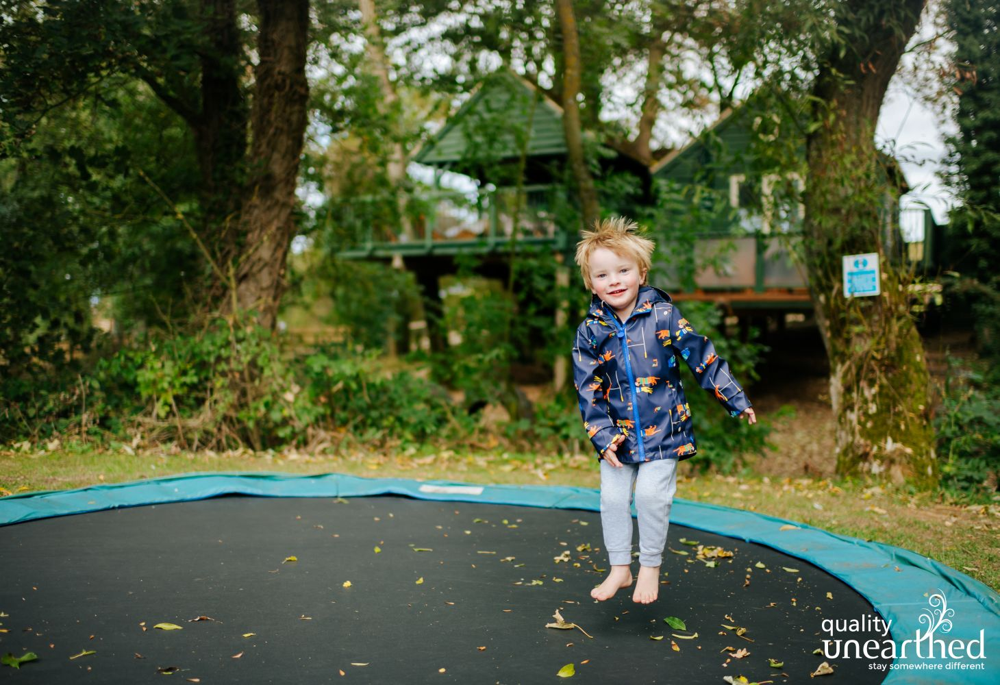 A little boy looks happy bouncing on the in ground trampoline, set in the Cotswold wood with the family treehouse in the background