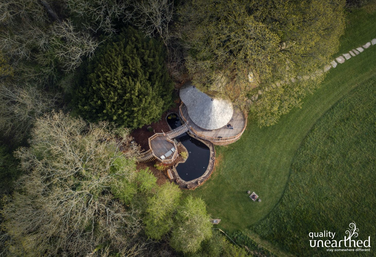 Aerial image of the treehouse sat alongside a Breacon Beacons woodland with a rope bridge linking to a terrace