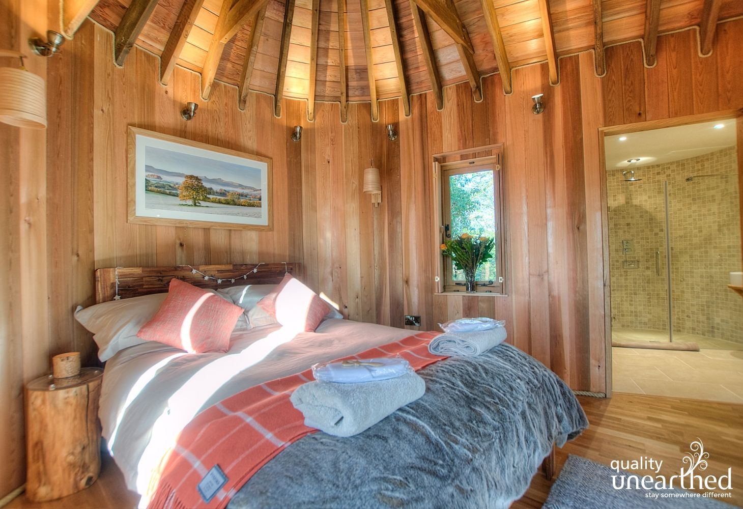 A handcrafted acacia double bed sits in a wooden treehouse with a vaulted ceiling. Doorway to shower room.