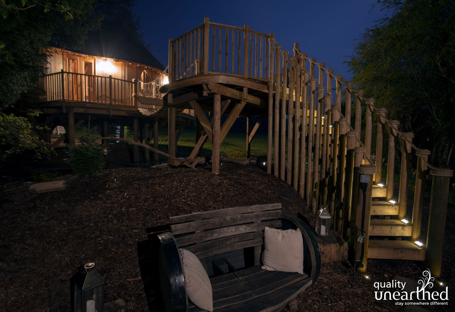 A wooden bench sits at the bottom of the circular stairs. A rope bridge leads to the treehouse with Breacon Beacons views