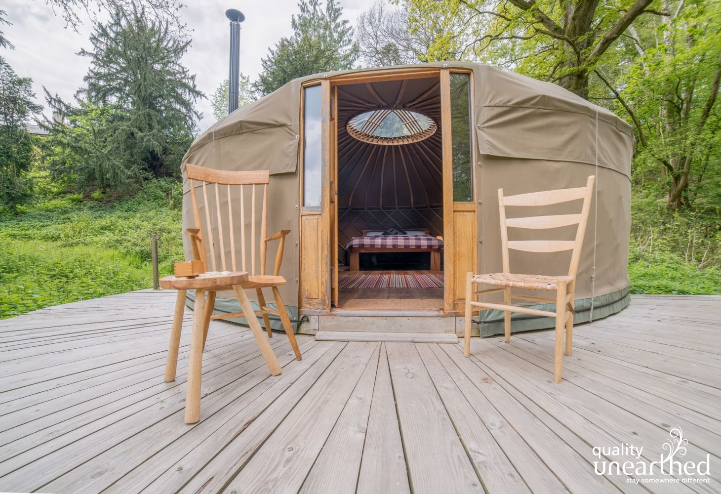 An image of the off-grid family sized yurt, sat on a spacious wooden terrace