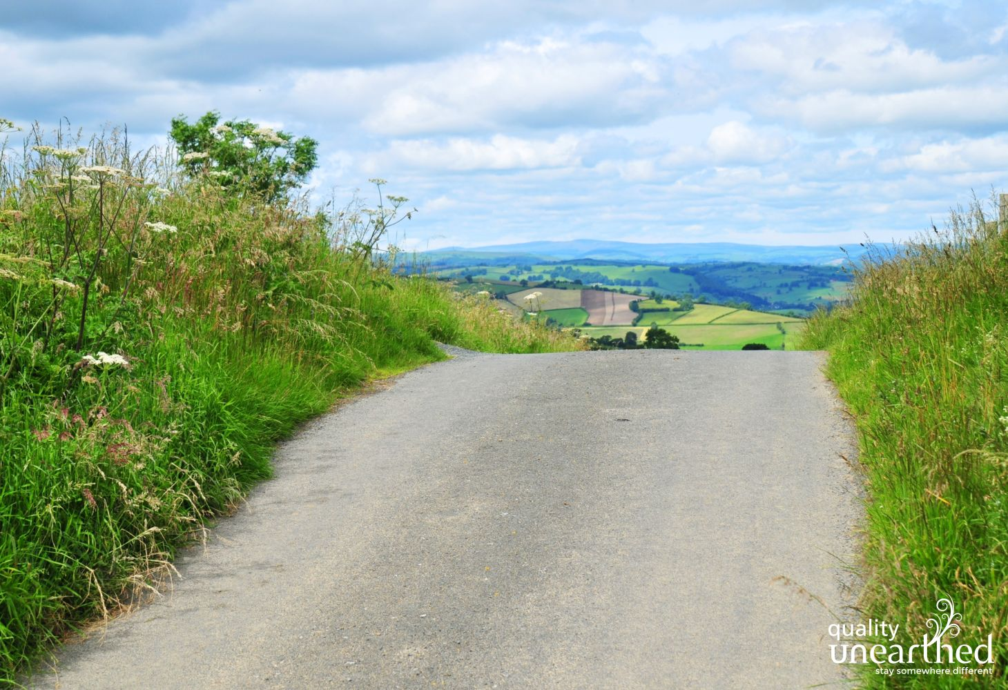 A view of the crest of a hill with the Mid Wales rolling countryside that surrounds the wooden cabin in the distance