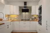 Contemporary white kitchen with wooden worktops and sage tiles