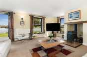 Spacious lounge with patio doors, TV, log burner and coffee table
