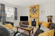 Luxury holiday cottage in the Llyn Peninsula - open plan lounge with TV, DVD player, Freeview and fire.