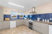 Holiday apartment overlooking golf course in Pembrokeshire, Wales. Modern kitchen with oven, dishwasher and fridge freezer.