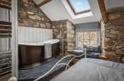 Double bedroom with roll top bath and exposed stone walls in traditional holiday cottage in Newport, Pembrokeshire. Sleeps 10