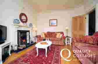 Welsh holiday cottage in Morfa Nefyn, on the Llyn Peninsula - lounge with Edwardian fireplace, TV and sofas. Dog friendly.