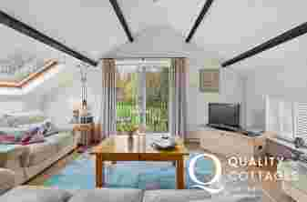 Lounge area with beamed ceiling, 3 seaters and 2 seater sofas, TV and private balcony